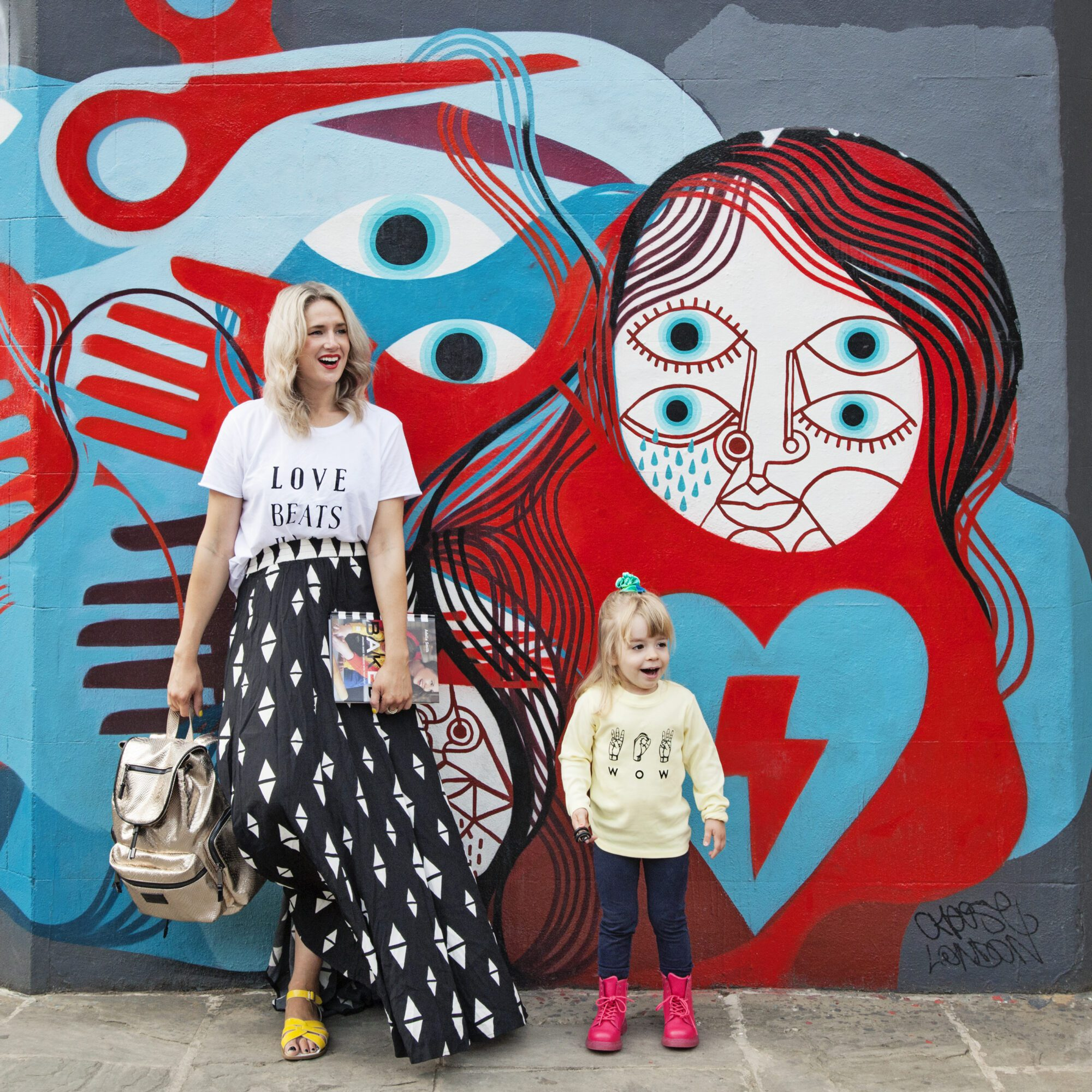 Anna Whitehouse, aka Mother Pukka and her mum Lucia, aka Grandmother Pukka, with daughter Mae in front of a wall painted by David Shilligham.